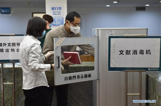 A reader (R) disinfects books at the National Library of China in Beijing, capital of China, May 12, 2020. The southern area of the National Library of China reopened to the public on Tuesday. Visitors need to make reservations via the social media application Wechat or phone calls, according to a notice from the library. (Xinhua/Chen Zhonghao)