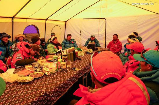 Team members gather for the announcement of a list who will climb to the peak of Mount Qomolangma at the advance camp at an altitude of 6,500 meters on Mount Qomolangma, May 18, 2020. A Chinese mountaineering team on Monday released a list of 12 people, including two surveyors, who will climb to the peak of Mount Qomolangma. If everything goes smoothly, they will arrive at the peak on May 22 to conduct surveys in gravity, global navigation satellite systems, weather and depths of ice and snow. Chen Gang and Wang Wei, both of whom are surveyors from the Ministry of Natural Resources, are on the list. If either of them manages to arrive at the peak, it will set a record for Chinese surveyors setting foot on the world's highest mountain peak, according to the team. The names of a support squad and a backup squad were also released on Monday. (Xinhua/Tashi Tsering)