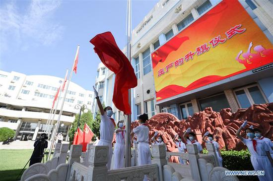 Students take part in a flag-raising ceremony at school in Beijing, capital of China, June 1, 2020. Students at their first and second grades of senior high schools, first and second grades of junior high schools and sixth grade of primary schools returned to school for this semester in Beijing on Monday. (Xinhua/Ju Huanzong)