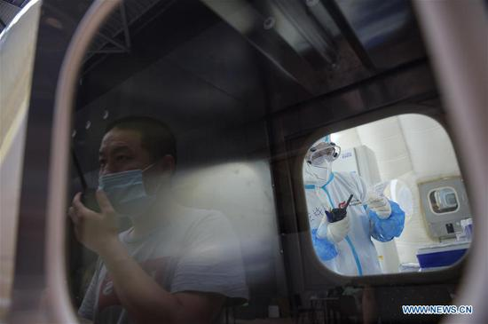 Members of staff work at a COVID-19 testing lab built with an air-inflated structure in Daxing District, Beijing, capital of China, June 22, 2020. A COVID-19 testing lab built with an air-inflated structure went into trial operation on Monday at a sports venue in Daxing District of Beijing to address the city's rising demand for nucleic acid tests after a cluster of infections were confirmed recently. The mobile Huoyan (Fire Eye) laboratory was built in two days over the weekend to accommodate 14 automated COVID-19 testing machines provided by Chinese biotech company BGI Genomics based in the city of Shenzhen, south China's Guangdong Province. (Xinhua/Peng Ziyang)