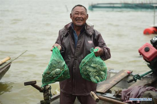 A fisherman shows crabs in Tuohu Town of Wuhe County, Bengbu City, east China's Anhui Province, Sept. 22, 2020. Hundreds of millions of Chinese farmers celebrated the third harvest festival on Tuesday. (Xinhua/Huang Bohan)