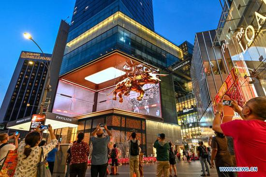 People take photos and video clips of the 3D golden bull video shown on the LED screen outside a shopping mall in Kuala Lumpur, Malaysia, Feb. 10, 2021. The year 2021 is the Year of the Ox according to the Chinese zodiac. With Chinese culture and food becoming increasingly popular, people not only in China, but all over the world also take part in the Chinese New Year celebrations. (Photo by Chong Voon Chung/Xinhua)