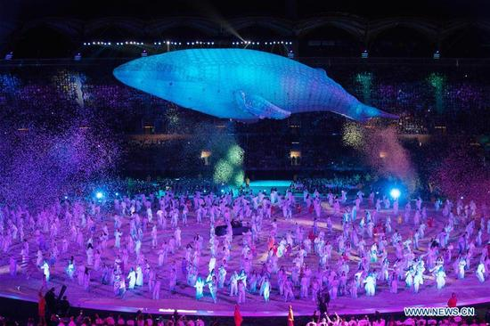 A figure in the shape of a white whale is seen during the opening ceremony of the 2018 Gold Coast Commonwealth Games at the Carrara Stadium in the Gold Coast, Australia, April 4, 2018. (Xinhua/Zhu Hongye)
