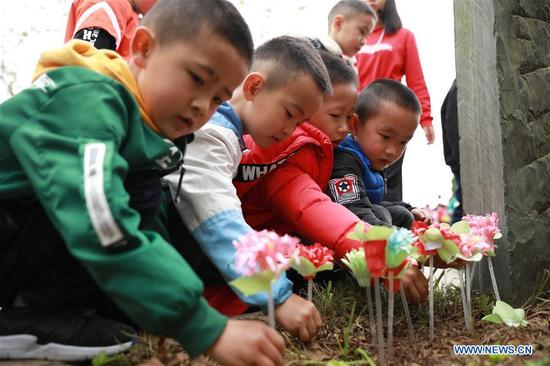 Children lay paper flowers at the tomb of martyrs in Danzhai County, southwest China's Guizhou Province, April 4, 2018. People mourn for the deceased as the Qingming Festival, the Chinese tomb-sweeping day, approaches. (Xinhua/Tang Ke)