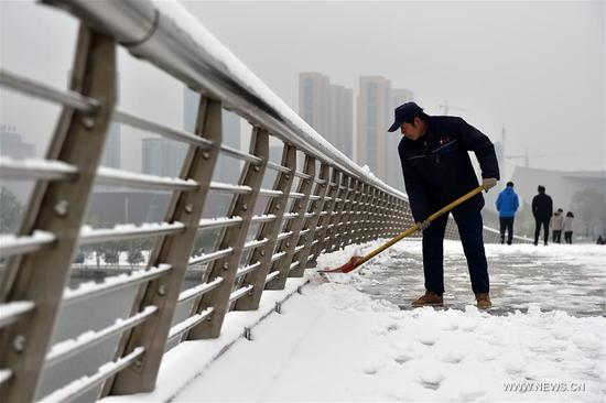 A man clears snow on a bridge in Taiyuan, capital of north China's Shanxi Province, April 5, 2018. A cold front brought snowfall to parts of China in these days. (Xinhua/Zhan Yan)