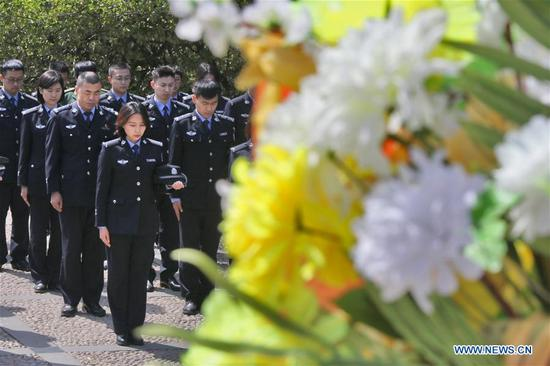 Police officers pay tribute in front of a monument of war heroes in Yantai, east China's Shandong Province, April 4, 2018. People mourn for the deceased as the Qingming Festival, the Chinese tomb-sweeping day, approaches. (Xinhua/Tang Ke)