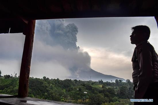 A man watches Mount Sinabung volcano spewing thick volcanic ash, seen from the town of Karo, North Sumatera, Indonesia, on April 6, 2018. (Xinhua/Sarianto)