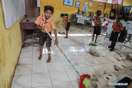 Pupils clean dust covering on floor at their school after Mount Sinabung volcano spewing volcanic ash on Friday in Karo, North Sumatera, Indonesia, on April 7, 2018. (Xinhua/Alberth Damanik)