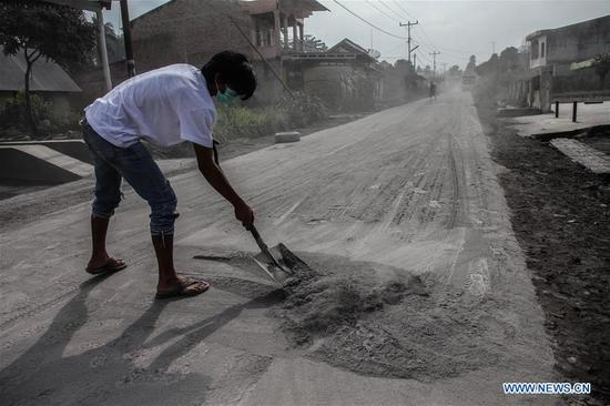 A man cleans dust covering on the street after Mount Sinabung volcano spewing volcanic ash on Friday in Karo, North Sumatera, Indonesia, on April 7, 2018. (Xinhua/Alberth Damanik)