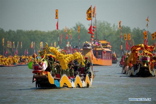 Boat team members perform a dragon dance during the Qintong Boat Festival in Taizhou, east China's Jiangsu Province, April 8, 2018. The Qintong Boat Festival in Taizhou originated in China's Southern Song Dynasty (1127-1279 A.D.) as a ceremony to commemorate war victims around the Qingming Festival. Nowadays, this tradition is well preserved and promoted, offering spectators a view of the gathering of hundreds of boats. (Xinhua/Tang Dehong)