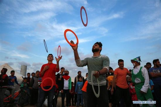 Palestinian youth play during the mass rally, known as the
