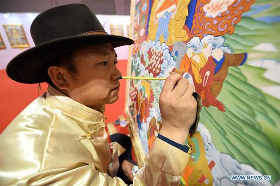 A thangka painter works during an art collection expo at Gansu international conference and exhibition center in Lanzhou, northwest China's Gansu Province, April 12, 2018. Over 50 thangka paintings were displayed at the expo that kicked off on Thursday. (Xinhua/Fan Peishen)