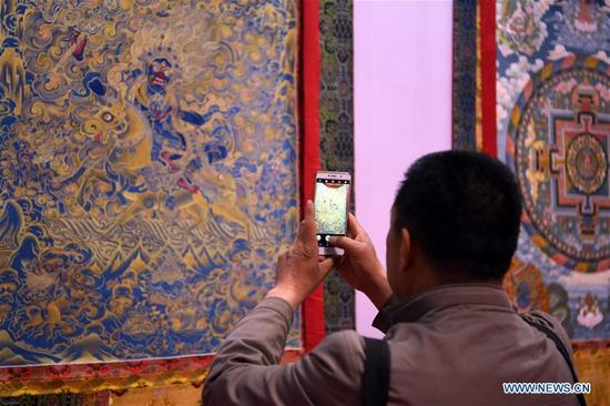 A man takes photo of thangka painting during an art collection expo at Gansu international conference and exhibition center in Lanzhou, northwest China's Gansu Province, April 12, 2018. Over 50 thangka paintings were displayed at the expo that kicked off on Thursday. (Xinhua/Fan Peishen)