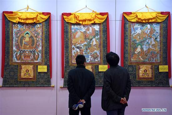 People view thangka paintings during an art collection expo at Gansu international conference and exhibition center in Lanzhou, northwest China's Gansu Province, April 12, 2018. Over 50 thangka paintings were displayed at the expo that kicked off on Thursday. (Xinhua/Fan Peishen)