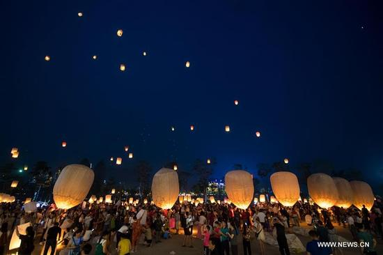 People fly Kongming lanterns, a kind of small hot-air paper balloons, by the Lancang River in Jinghong City, southwest China's Yunnan Province, April 13, 2018, to celebrate the New Year of the calendar of the Dai ethnic group. (Xinhua/Hu Chao)