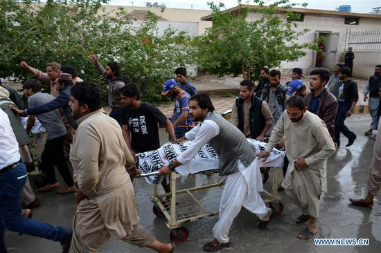 People transfer the body of a victim to a hospital following a shooting attack in southwest Pakistan's Quetta, on April 15, 2018. At least two persons were killed and five others injured on Sunday in a shooting attack in Pakistan's Quetta, local media and police said. (Xinhua/Asad)