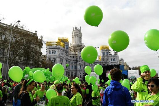 Runners rest in front of the city hall after they finished the Madrid Race in March Against Cancer in Madrid, Spain, April 15, 2018. The race was held by the Spanish Association Against Cancer, with the purpose of raising public attention on anticancer and having healthy lifestyle. (Xinhua/Guo Qiuda)