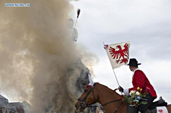A guildsman rides a horse around a symbolic snowman during the Sechselauten, a local Spring festival, in Zurich, Switzerland, on April 16, 2018. The Sechselauten is a traditional festival marking the end of winter with a parade of guilds in historical costumes and the burning of a symbolic snowman. (Xinhua/Michele Limina)