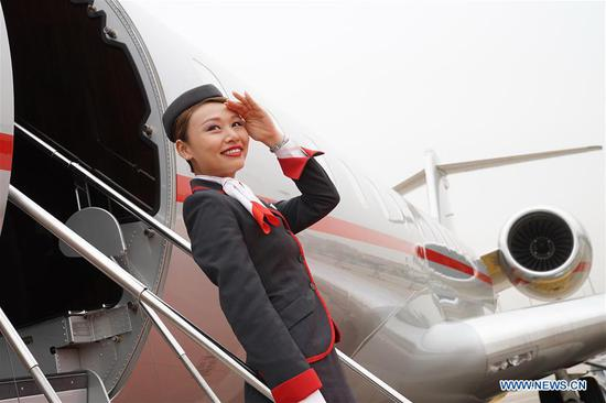 An exhibitor poses for photos in front of an aircraft to be displayed in the Asian Business Aviation Conference and Exhibition (ABACE) at Shanghai Hongqiao International Airport in east China's Shanghai, April 16, 2018. The ABACE is expected to be held here from April 17 to 19, attracting over 170 companies around the world to participate in the exhibition. (Xinhua/Chen Fei)