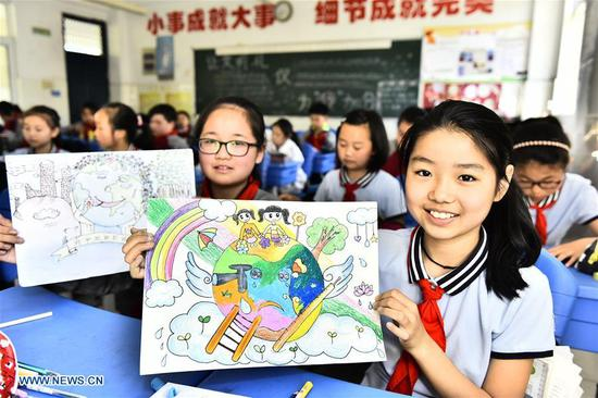 Students show their painting works in a drawing activity for the upcoming Earth Day at Xincheng Primary School in Jinggang Town of Shushan District in Hefei City, capital of east China's Anhui Province, April 19, 2018. Many schools in China hold various Earth Day-themed drawing activities to welcome the Day, which is celebrated yearly on April 22. (Xinhua/Ge Yinian)