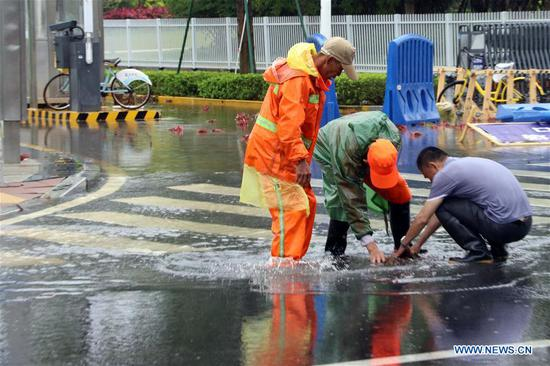 People clean the sewer in order to drain off the water in Xiamen, southeast China's Fujian Province, May 7, 2018. Flash floods broke out here due to heavy rainfall. (Xinhua/Zeng Demeng)