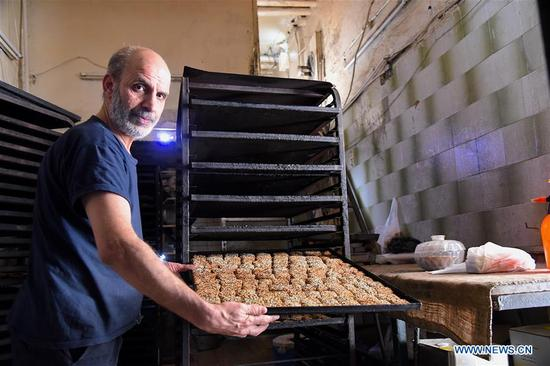 A baker works in an ancient bakery in the old city of Aleppo, north Syria, on May 6, 2018. This bakery produces various types of cookies and bagels, the most famous of which is sesame seed breadsticks, known as Kaak al-Sakhaneh in Arabic. They were the most favorite food for the travelers and merchants on the ancient Silk Road. (Xinhua/Hummam Sheikh Ali)