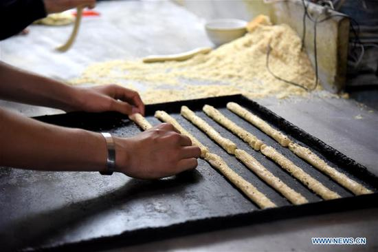 A baker prepares sesame seed breadsticks in an ancient bakery in the old city of Aleppo, north Syria, on May 6, 2018. This bakery produces various types of cookies and bagels, the most famous of which is sesame seed breadsticks, known as Kaak al-Sakhaneh in Arabic. They were the most favorite food for the travelers and merchants on the ancient Silk Road. (Xinhua/Hummam Sheikh Ali)