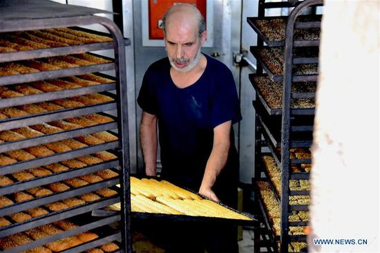 A baker checks sesame seed breadsticks in an ancient bakery in the old city of Aleppo, north Syria, on May 6, 2018. This bakery produces various types of cookies and bagels, the most famous of which is sesame seed breadsticks, known as Kaak al-Sakhaneh in Arabic. They were the most favorite food for the travelers and merchants on the ancient Silk Road. (Xinhua/Hummam Sheikh Ali)