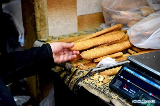 Photo taken on May 6, 2018 shows sesame breadsticks in an ancient bakery in the old city of Aleppo, north Syria. This bakery produces various types of cookies and bagels, the most famous of which is sesame seed breadsticks, known as Kaak al-Sakhaneh in Arabic. They were the most favorite food for the travelers and merchants on the ancient Silk Road. (Xinhua/Hummam Sheikh Ali)