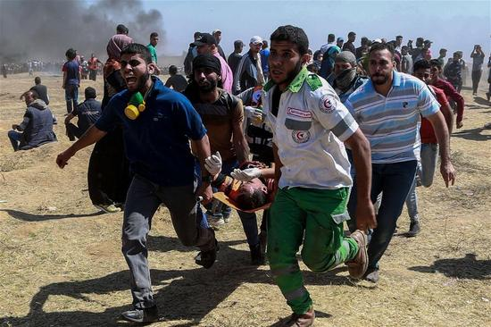 Palestinian medics and protesters carry an injured man during clashes with Israeli troops near the Gaza-Israel border, east of Gaza City, on May 14, 2018. More than 40 Palestinians, including children, were killed Monday in a day of violent clashes with Israeli forces on Israel's southern border with Gaza, according to the Gaza health ministry. (Xinhua/Wissam Nassar)