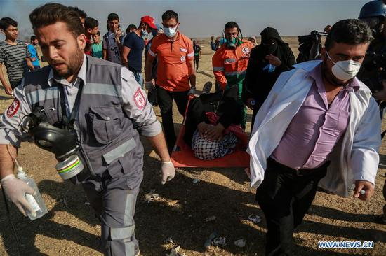"Palestinians carry an injured man during clashes with Israeli troops near the Gaza-Israel border, east of Gaza City, on May 15, 2018. Some 4,000 Palestinians Tuesday participated in the protests along the Gaza Strip border at five locations, said the Israeli army. The protests marked the ""Nakba Day,"" which means catastrophe, referring to the displacement of hundreds of thousands of Palestinians in the war surrounding the creation of Israel in 1948. (Xinhua)"
