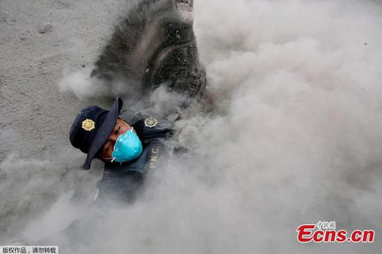 A police officer stumbles while running away from a new pyroclastic flow spewed by the Fuego volcano in the community of San Miguel Los Lotes in Escuintla, Guatemala, June 4, 2018. An estimated 25 people, including at least three children, were killed and nearly 300 injured on Sunday in the most violent eruption of Guatemala's Fuego volcano in more than four decades, officials said. (Photo/Agencies)