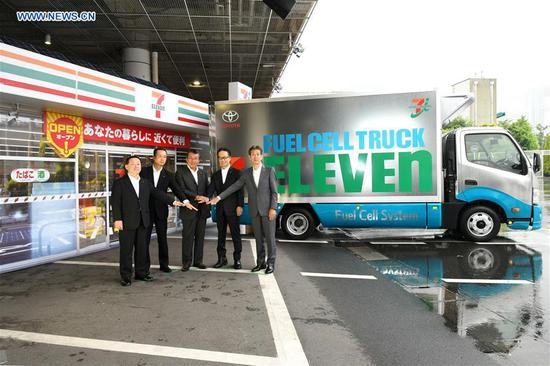 Guests take group photos in front of Toyota Motor Corp's hydrogen fuel cell truck for pilot project with Seven-Eleven in Tokyo, Japan, June 6, 2018. (Xinhua/Hua Yi)