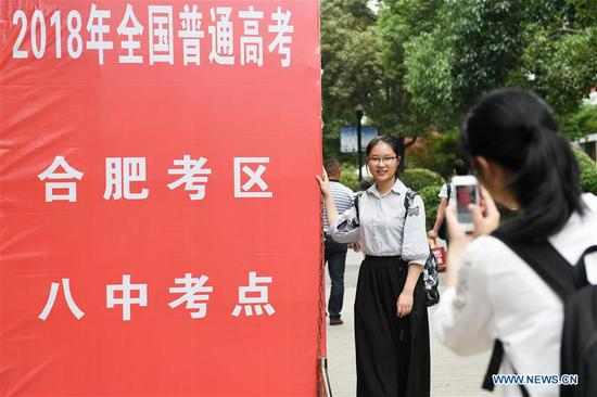 A student poses for photos after the exam at a middle school in Hefei, east China's Anhui Province, June 8, 2018. The national college entrance examination ended in some places of China on Friday. (Xinhua/Zhang Duan)