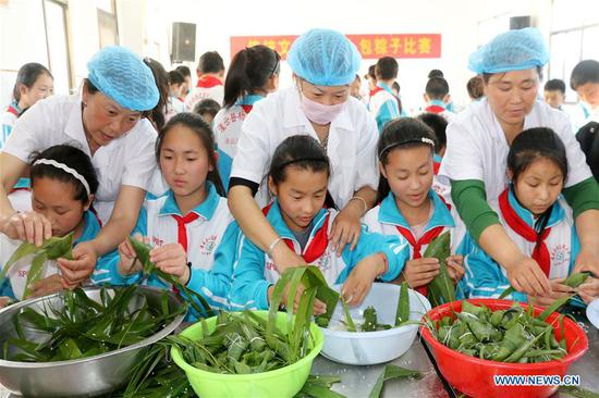 Pupils make zongzi, a pyramid-shaped dumpling made of glutinous rice wrapped in bamboo or reed leaves, under the direction of volunteers to celebrate the Duanwu Festival at Qianhe Primary School in Sidui Town in Guanyun County, east China's Jiangsu Province, June 11, 2018. (Xinhua/Wu Chenguang)