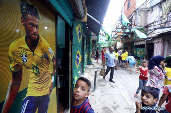 A boy stands by the poster of a Brazilian footballer in Beirut, Lebanon, on June 12, 2018. Although Lebanon's national team is not qualified for the 2018 Russia World Cup finals, the Lebanese are still passionate about football and greet the event in different ways. (Xinhua/Bilal Jawich)