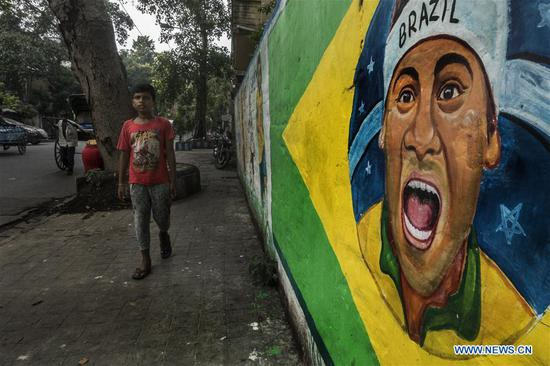 A pedestrian walks past a wall graffiti of a Brazilian footballer before the upcoming Russia 2018 World Cup finals, in Kolkata, India, June 12, 2018. (Xinhua/Tumpa Mondal)