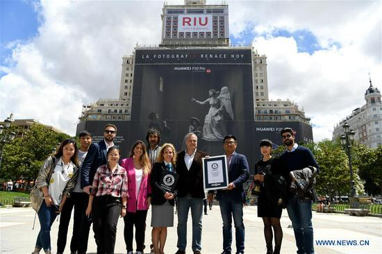 People pose for photos with the Guinness World Record certificate in front of the Huawei P20 Pro advertisement outside a building in Madrid, Spain, June 12, 2018. Huawei on Tuesday received a Guinness World Record certificate for