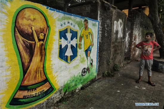 A pedestrian stands in front of a wall graffiti of a Brazilian footballer before the upcoming Russia 2018 World Cup finals, in Kolkata, India, June 12, 2018. (Xinhua/Tumpa Mondal)