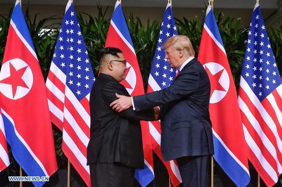 Top leader of the Democratic People's Republic of Korea (DPRK) Kim Jong Un (L) shakes hands with U.S. President Donald Trump in Singapore before the first-ever DPRK-U.S. summit, on June 12, 2018. (Xinhua/The Straits Times)