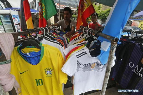 A vendor sells flags and T-shirts in Beirut, Lebanon, on June 12, 2018. Although Lebanon's national team is not qualified for the 2018 Russia World Cup finals, the Lebanese are still passionate about football and greet the event in different ways. (Xinhua/Bilal Jawich)