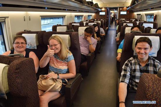 Passengers take the G7 new longer Fuxing bullet train from Beijing to Shanghai, July 1, 2018. The new longer Fuxing bullet train ran on the Beijing-Shanghai line for the first time on Sunday. With a designed speed of 350 kilometers per hour, the new train measures more than 400 meters in length and has 16 carriages, twice as many as current ones. It can carry nearly 1,200 passengers. (Xinhua/Yang Baosen)