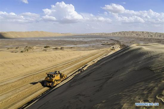 Vehicles work at a desert road construction site in Taklimakan desert in northwest China's Xinjiang Uygur Autonomous Region, July 5, 2018. An over 300-km-long desert road, linking Xinjiang's Yuli County to remote Qiemo County, is now under construction. It's the third that-kind-of road crossing China's largest desert Taklimakan nicknamed