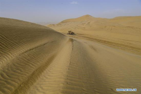 A vehicle works at a desert road construction site in Taklimakan desert in northwest China's Xinjiang Uygur Autonomous Region, July 5, 2018. An over 300-km-long desert road, linking Xinjiang's Yuli County to remote Qiemo County, is now under construction. It's the third that-kind-of road crossing China's largest desert Taklimakan nicknamed