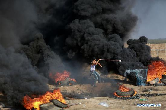 A Palestinian protester hurls stones at Israeli troops during clashes in eastern Gaza City, on July 6, 2018. A new round of clashes broke out Friday afternoon between Palestinian protesters and Israeli soldiers in eastern Gaza City, close to the border with Israel, according to eyewitnesses and local media reports. (Xinhua)