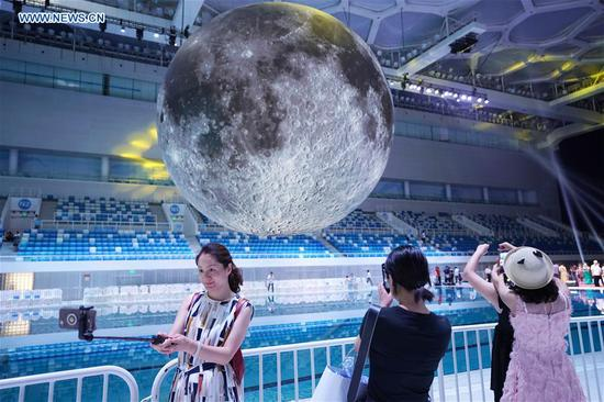 Visitors take photos of a huge moon model during an exhibition on moon held at the National Aquatic Center or