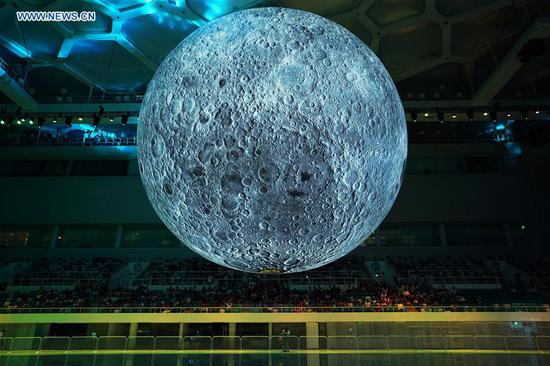 Visitors view a huge moon model during an exhibition on moon held at the National Aquatic Center or