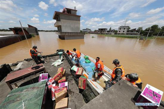 Rescue workers transport relief supplies in Dongxiang Disctrict of Fuzhou City, east China's Jiangxi Province, July 8, 2018. Flood caused by heavy rain damaged crops and housings in Maxu Township of Dongxiang and rescue groups were set up to help the affected people. (Xinhua/He Jianghua)