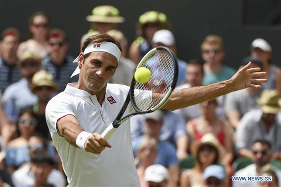 Roger Federer of Switzerland hits a return during the men's singles fourth round match against Adrian Mannarino of France at the Wimbledon Championships 2018 in London, Britain, on July 9, 2018. Roger Federer won 3-0. (Xinhua/Stephen Chung)