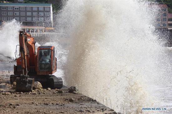 A staff worker reinforces a dike at a scenic spot in Wenling City, east China's Zhejiang Province, July 10, 2018. China Meteorological Administration on Tuesday issued this year's first red alert for typhoon as the Typhoon Maria or the 8th of the year approaches the Chinese coast. Typhoon Maria is likely to sweep Taiwan, Fujian, Jiangxi and part of Zhejiang on Tuesday and Wednesday.(Xinhua/Jin Yunguo)